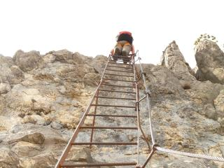 a man climbs a ladder at the summit of a mountain
