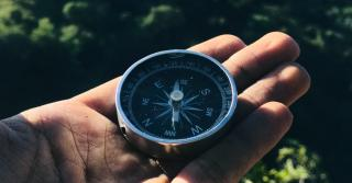 A man holding a compass in his hand