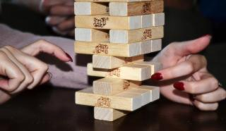 Hands moving a Jenga piece