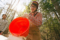 A student in the woods pouring water from one container to another